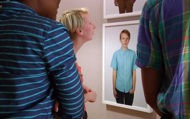 """אילוסטרציה, משתתפ/ת בתערוכה על נזילות מגדרית צופה בדיוקנו/ה, ארה""""ב, 2014 (צילום: AP Photo/Jay Reeves)"""