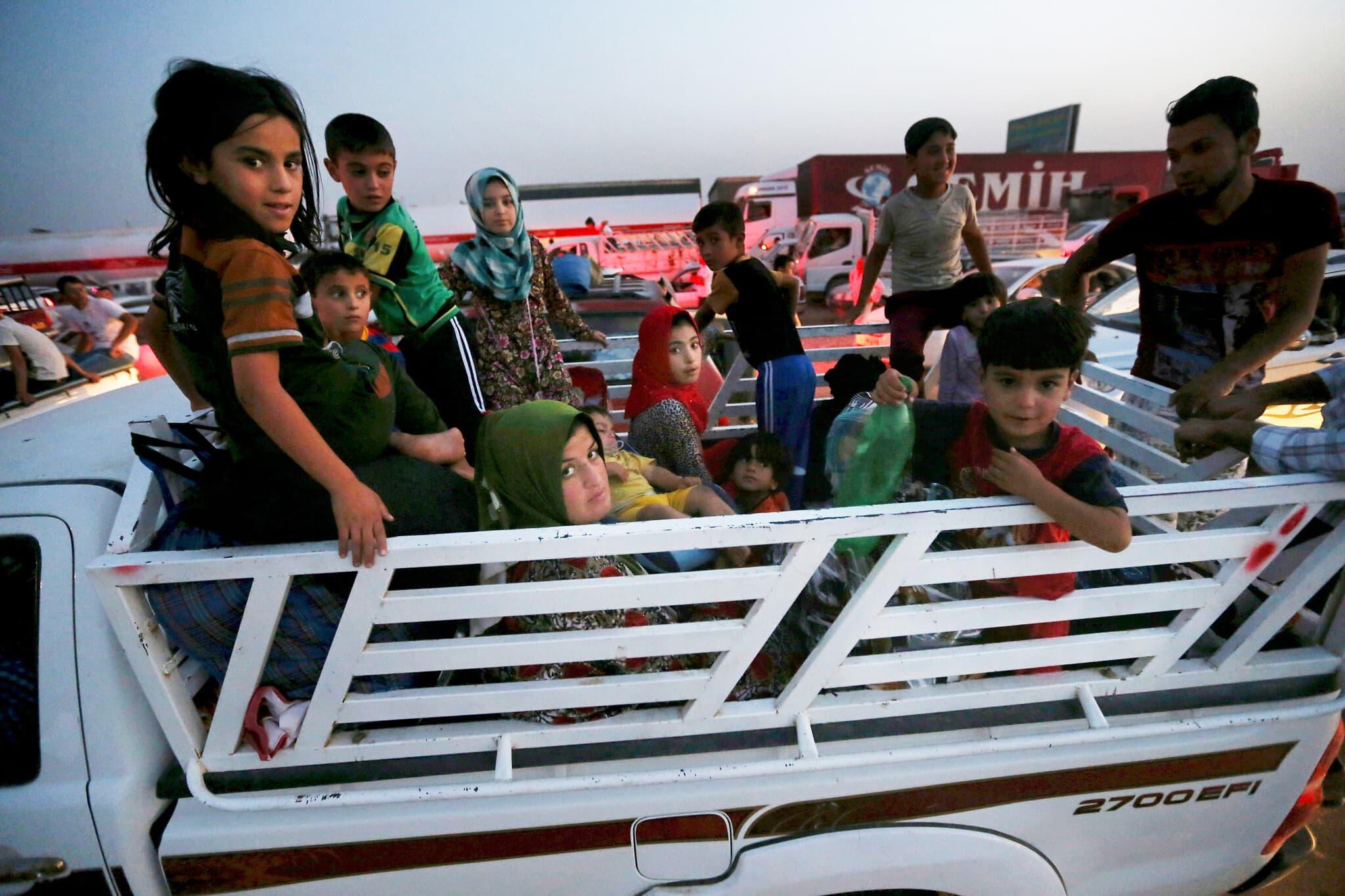 """עיראקים נסים ממוסול אחרי כניסת כוחות דאע""""ש לעיר, ב25 ביוני 2014- (צילום: AP Photo/Hussein Malla)"""