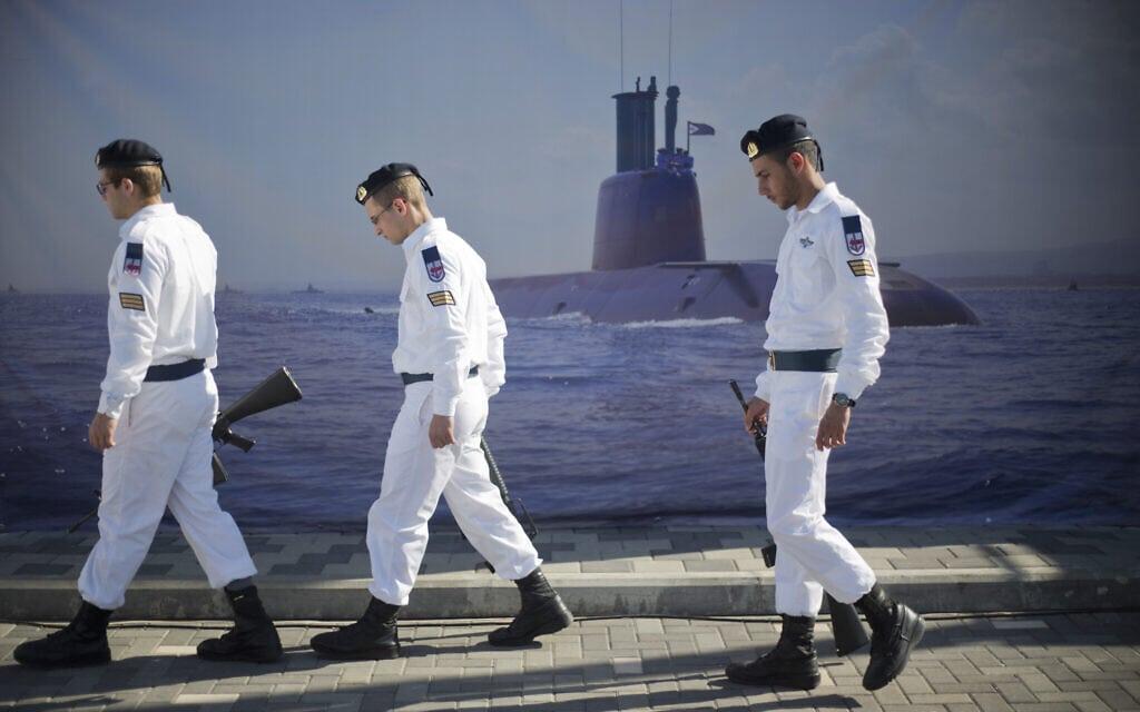 """חילי חיל הים ממתינים להגעת הצוללת אח""""י רהב. מאחוריהם – פוסטר של צוללת. 2016 (צילום: AP Photo/Ariel Schalit)"""