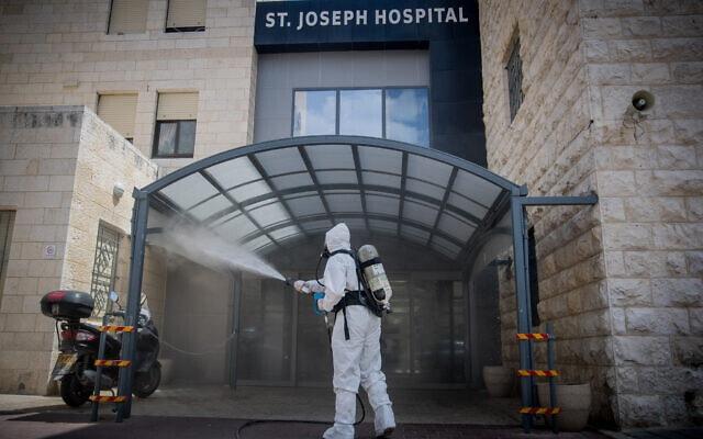 לוחמי אש ישראלים מחטאים את הכניסה לבית החולים סנט ג'וזף במזרח ירושלים, כאמצעי הגנה נגד התפשטות הקורונה. אפריל, 2020 (צילום: יהונתן סינדל/ פלאש 90)
