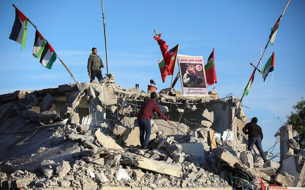 פלסטינים עומדים על הריסות ביתה של משפחת המחבל קסאם אל-ברגותי, ב-11 במאי 2020 (צילום: פלאש90)