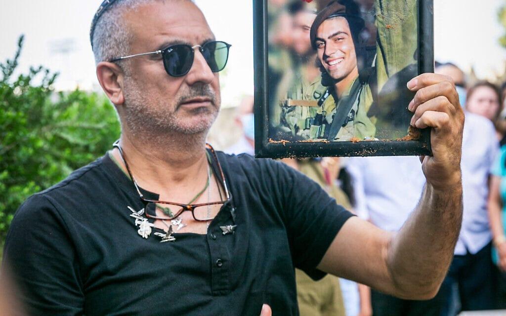 אביו של עמית בן יגאל אוחז בתמונת בנו המובא למנוחות, מאי 2020 (צילום: פלאש 90)