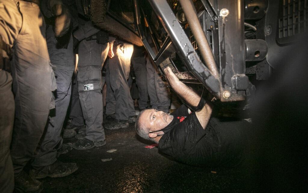 """גונן בן יצחק נשכב מתחת למכתז""""ית בהפגנה בבלפור (צילום: אוליבייה פיטוסי/פלאש 90)"""