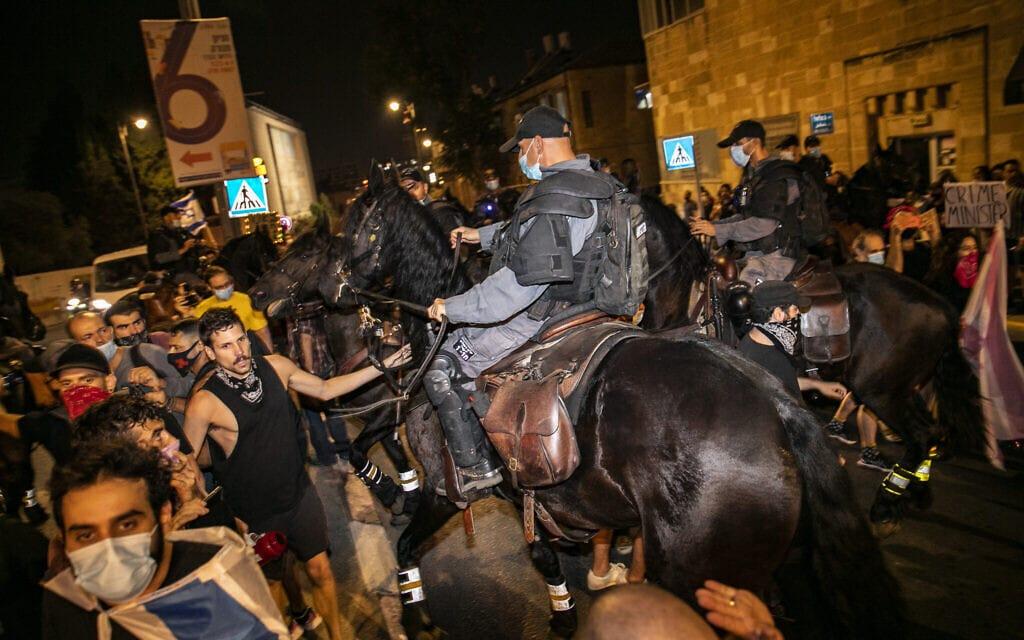 פרשים משטרתיים רוכבי אל תוך המפגינים כדי לפזר את המחאה. 22 באוגוסט 2020 (צילום: אוליבייה פיטוסי/פלאש90)