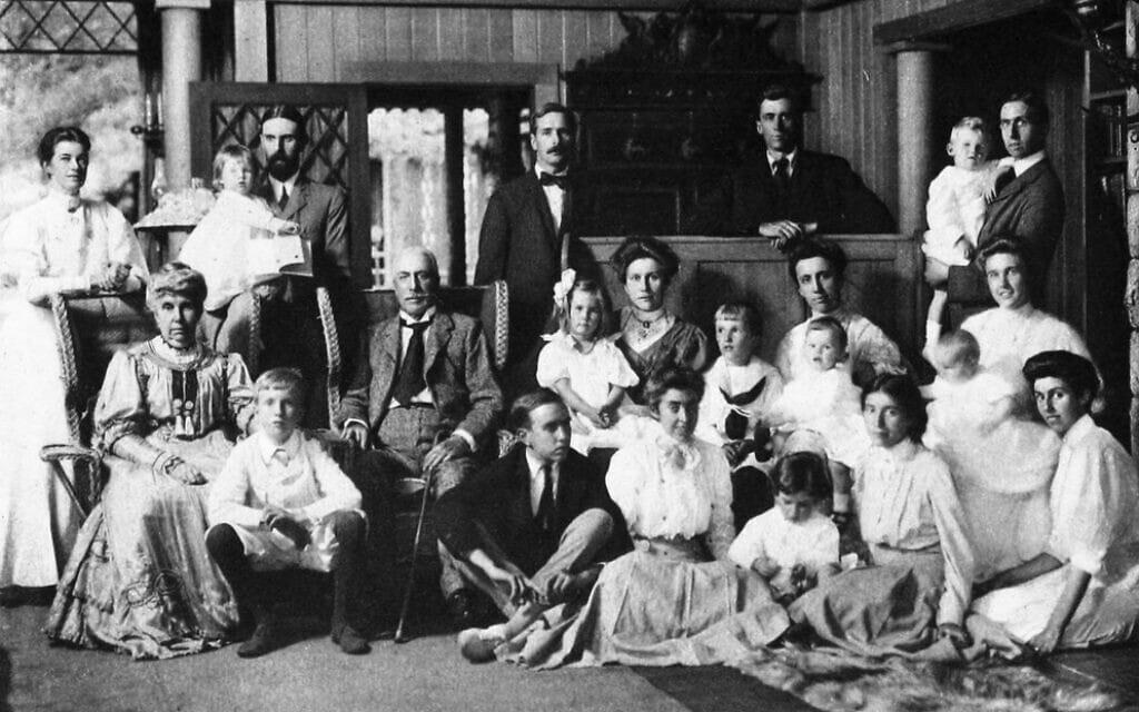 הוריו של גראהם סטוקס (יושבים, משמאל ובמרכז) עם ילדיהם, חתניהם וכלותיהם ונכדיהם באחוזה שלהם בהרי אדירונדאק ב-1907. גראהם עומד כשידיו מונחות על הדלפק, רוז פסטור יושבת על הרצפה, שנייה מימין (צילום: אלבומי סטוקס, כרך 3, אנסון פלפס סטוקס)