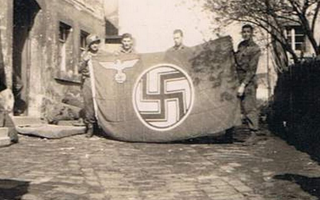 אביה של המחברת, טוראי אלכסנדר ברויאר (משמאל), עם דגל נאצי שהחרים עם חבריו בעיירה גרמנית קטנה (צילום: באדיבות הדי אברמוביץ)