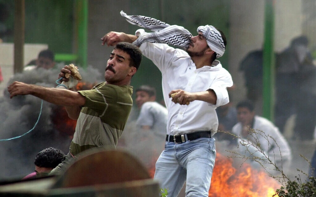 """פלסטינים משליכים אבנים על כוחות צה""""ל ברמאללה בעקבות עליית אריאל שרון להר הבית, ב-28 בספטמבר 2000 (צילום: AP Photo/Elizabeth Dalziel)"""