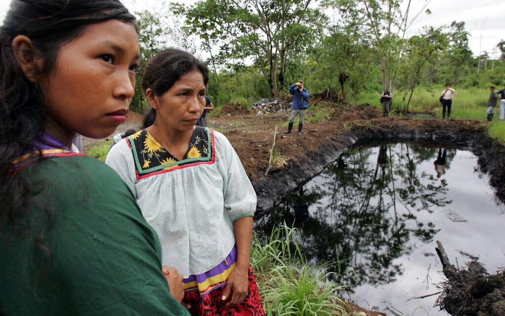 נשים עומדות ליד בריכת נפט באזור האמזונס של אקוודור, 20 באוקטובר 2005 (צילום: AP Photo/Dolores Ochoa)