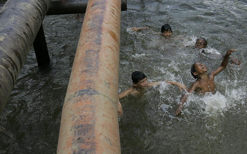 """ילדים משחקים בנהר שבו צינורות נפט עוברים מעל פני השטח באקוודור, אוגוסט 2008. נשיא אקוודור התייצב לצד 30,000 התובעים בתביעה הייצוגית שכונתה """"צ'רנוביל של האמזונס"""", בגלל הרעלה אטית של יערות גשם עם מיליוני ליטרים של נפט ומיליארדי שפכים רעילים (צילום: AP Photo/Dolores Ochoa)"""