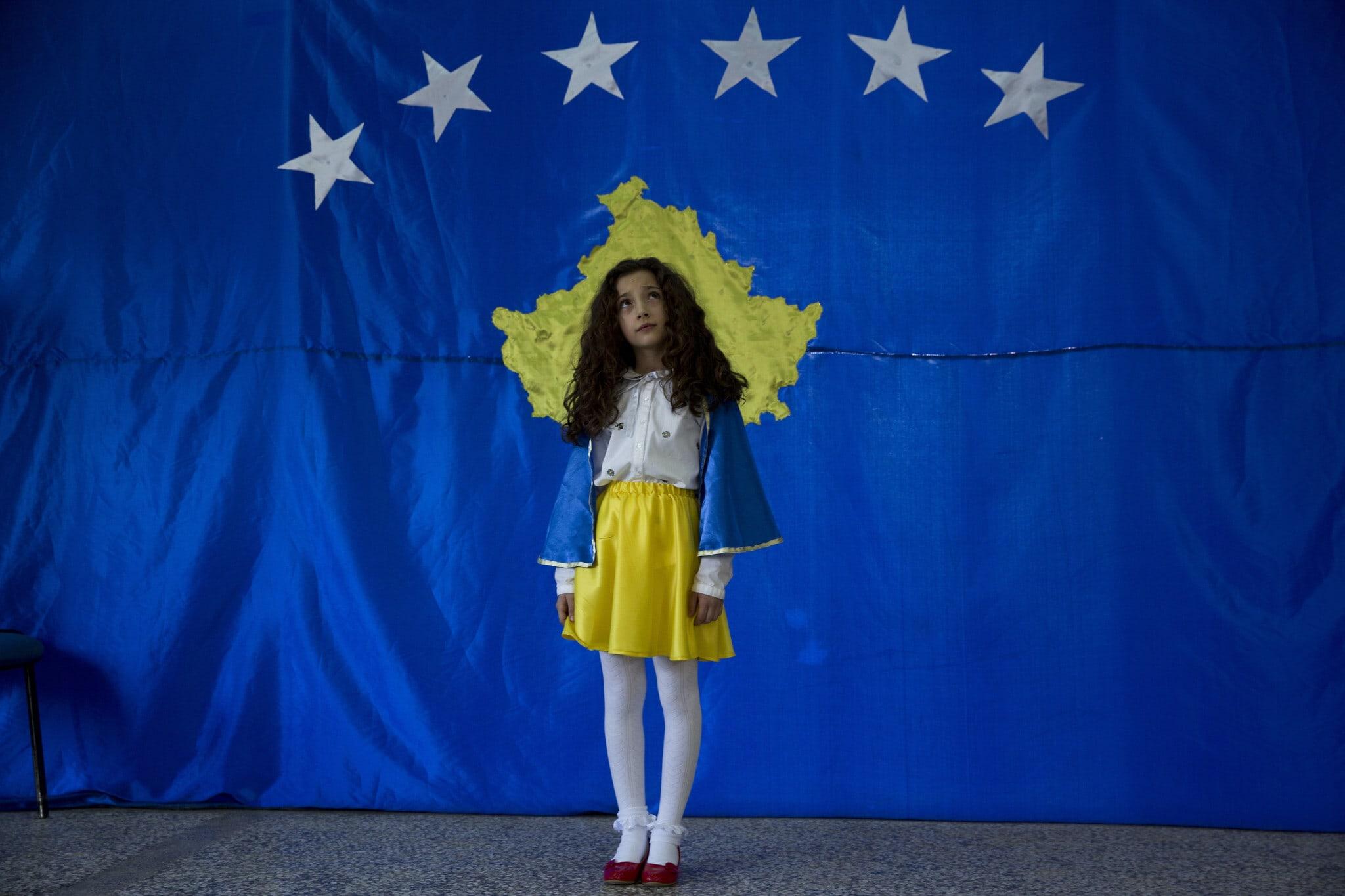 סופי בת העשר מתייצבת לפני דגל קוסובו במהלך טקס חגיגת יום העצמאות העשירי של קוסובו בבית ספרה, 2018. סופי הייתה הילדה הראשונה שנולדה בקוסובו העצמאית (צילום: AP Photo/Visar Kryeziu)