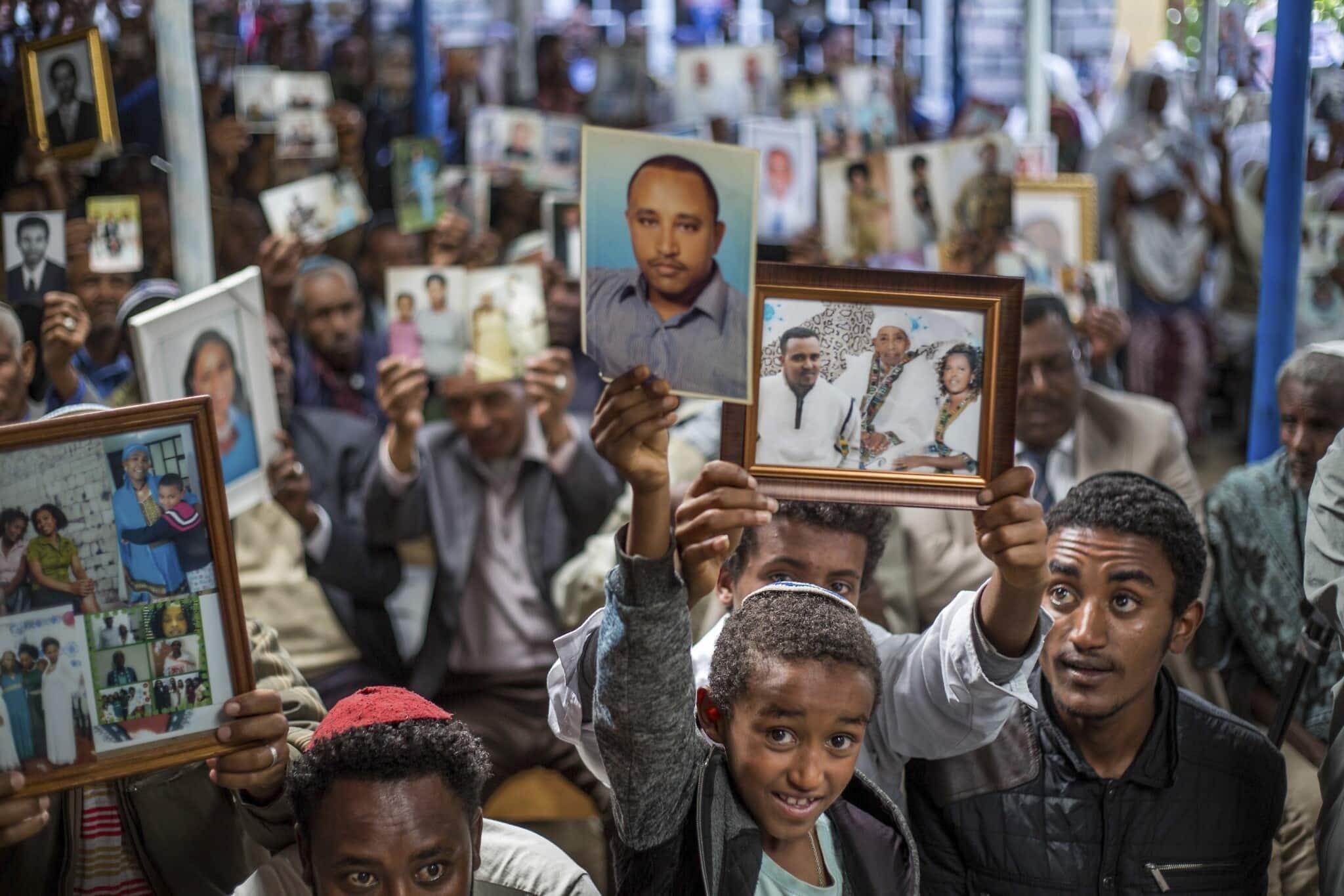 חברי הקהילה היהודית באתיופיה מציגים תמונות של קרוביהם בישראל, במהלך אירוע סולידריות בבית הכנסת באדיס אבבה, פברואר 2018. (צילום: AP Photo / Mulugeta Ayene)