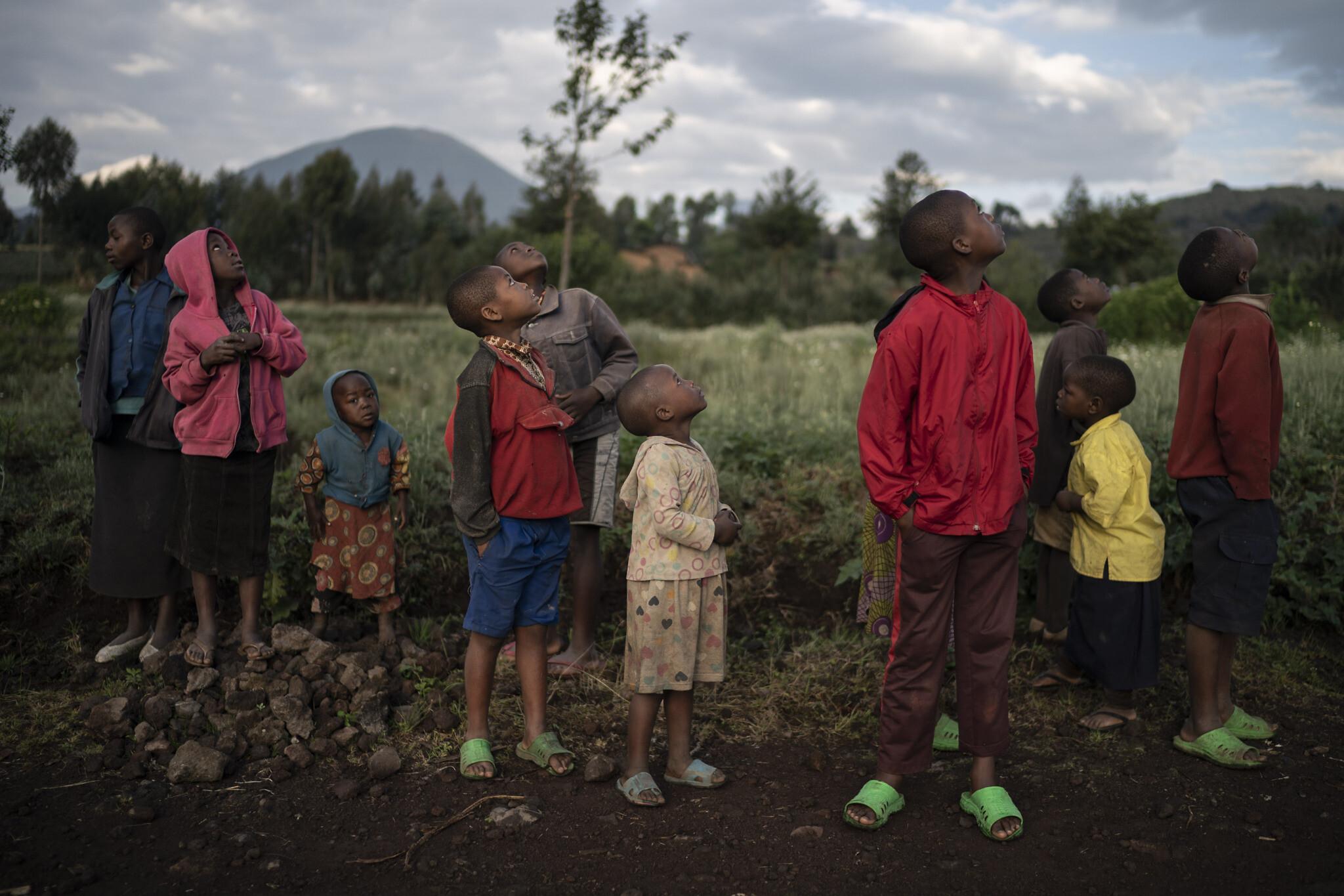 """אילוסטרציה, ילדים צופים במזל""""ט שטס ליד הפארק הלאומי בקיניגי, רואנדה, ספטמבר 2019 (צילום: AP Photo/Felipe Dana)"""