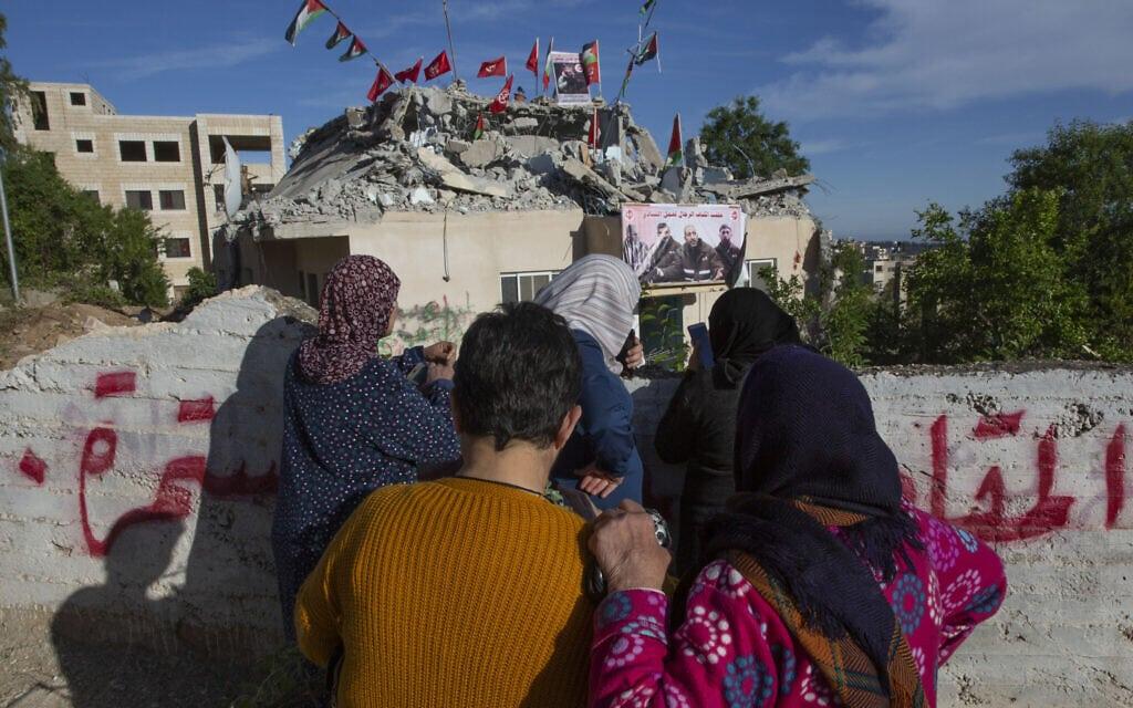 """אילוסטרציה, נשים פלסטיניות מסתכלות על בית מחבל שנהרס בחלקו על ידי צה""""ל בכפר קובאר ליד רמאללה, 11 במאי 2020 (צילום: AP Photo/Nasser Nasser)"""