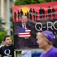 תומכי QAnon ברומניה משתתפים בעצרת נגד צעדי הממשלה למניעת התפשטות הקורונה בבוקרשט, 10 באוגוסט 2020 (צילום: AP Photo)