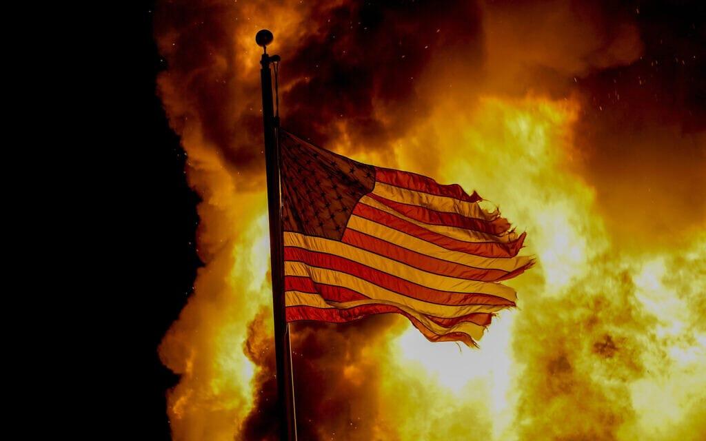 דגל ארצות הברית מוקף בלהבות בקנושה, 24 באוגוסט 2020 (צילום: AP Photo / Morry Gash)