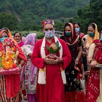 הודים במסכות נושאים מנחה לאל ההינדי גאנשה, אוגוסט 2020 (צילום: AP Photo / Ashwini Bhatia)