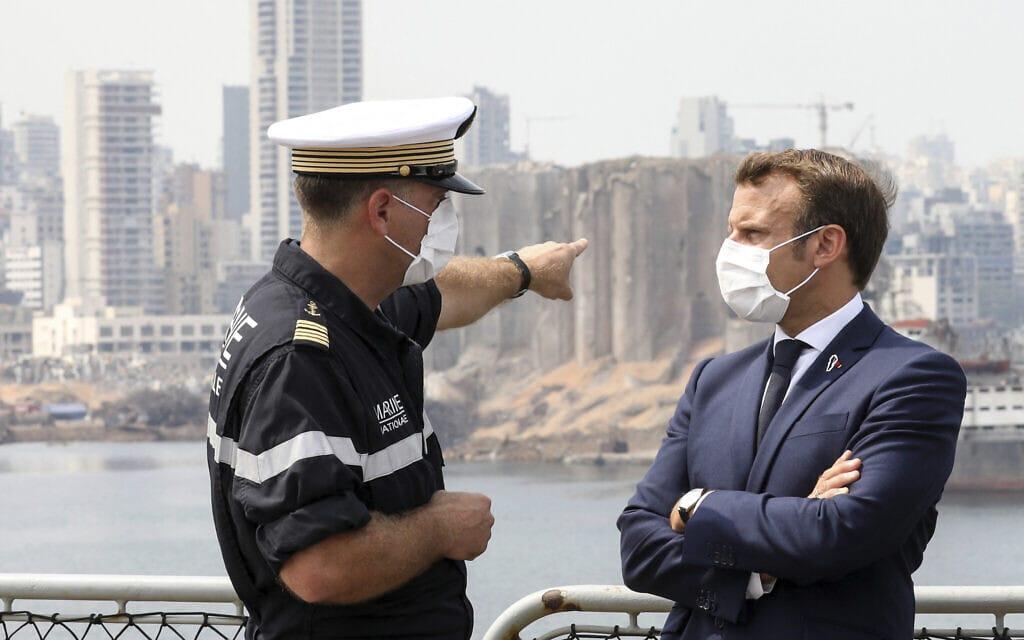 נשיא צרפת עמנואל מקרון מחוץ לנמל ביירות, יום שלישי, 1 בספטמבר 2020. לשמאלו, קצין חיל הים הצרפתי (צילום: סטפן למוטון דרך AP)