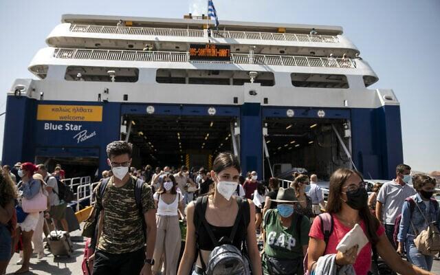 נוסעים במסיכות פנים מגיעים לנמל פיראוס, סמוך לאתונה. 2 בספטמבר 2020 (צילום: AP Photo/Yorgos Karahalis)