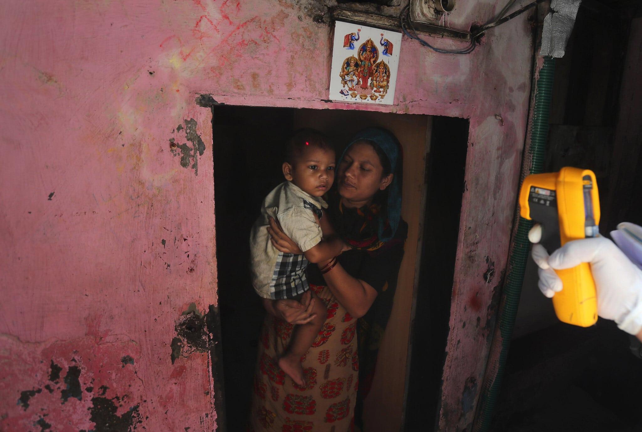 עובד בריאות בודק תסמינים של COVID-19 בדאראווי, אחת משכונות העוני הגדולות במומביי, ספטמבר 2020 (צילום: AP Photo/Rafiq Maqbool)