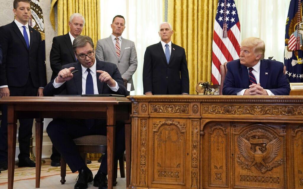 הנשיא דונלד טראמפ מאזין לנשיא סרביה אלכסנדר ווצ'יץ לאחר שהשתתף בטקס חתימה במשרד הסגלגל של הבית הלבן, 4 בספטמבר 2020 (צילום: AP Photo/Evan Vucci)