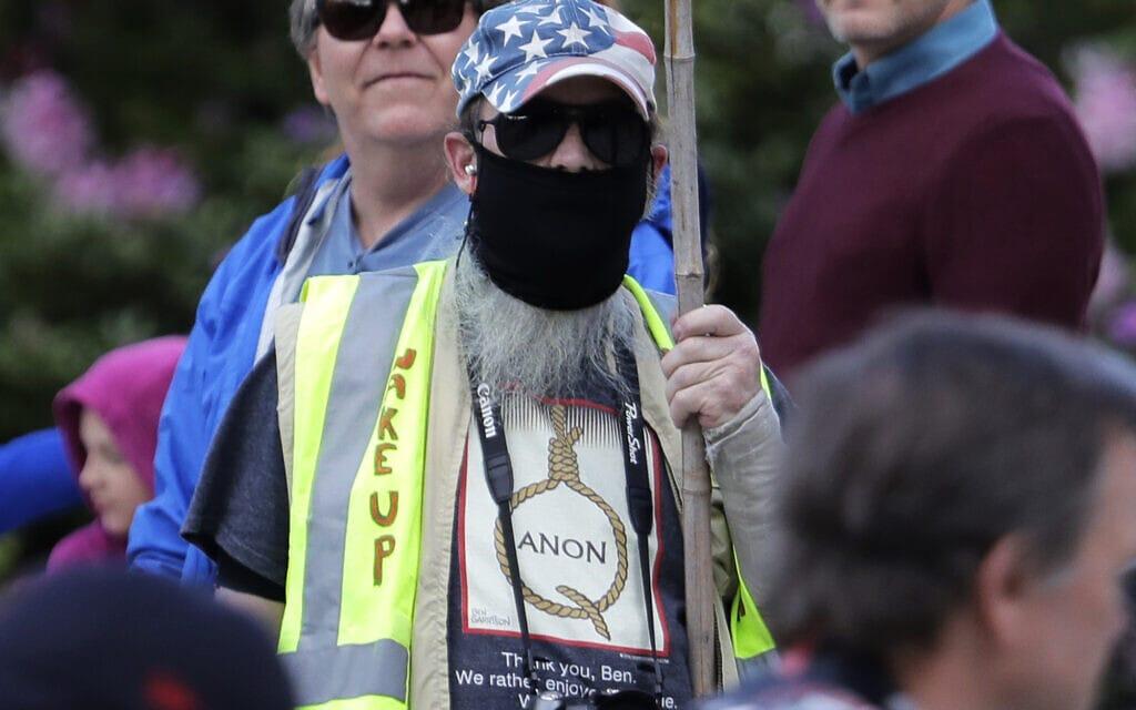 14 במאי 2020: תומך QAnon בעצרת מחאה נגד מגבלות הקורונה באולימפיה, וושינגטון (צילום: AP Photo/Ted S. Warren)