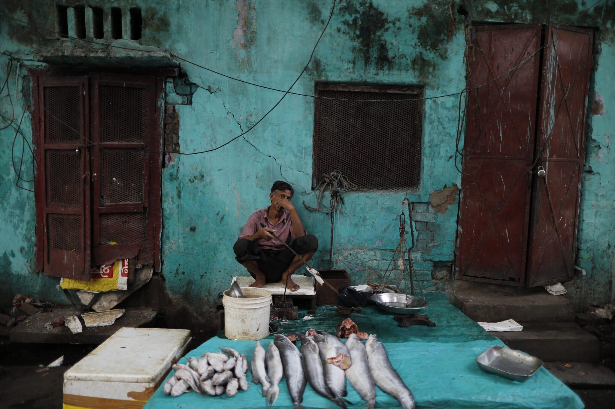 מוכר דגים ממתין ללקוחות בדוכן הדרך שלו בלוקנוב, הודו, ספטמבר 2020, לאחר שהכלכלה הצטמצמה בכמעט 24% ברבעון האחרון (צילום: AP Photo/Rajesh Kumar Singh)