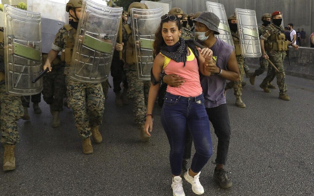 מפגין נגד השלטון מגן על חברתו מפני חיילים במהלך מחאה ליד ביירות, 12 בספטמבר 2020 (צילום: AP Photo/Bilal Hussein)