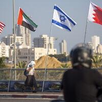 אישה עם מסכת פנים נגד חולפת על פני דגלי אמריקה, איחוד האמירויות, ישראל ובחריין בגשר השלום בנתניה, 14 בספטמבר 2020 (צילום: AP Photo/Ariel Schalit)