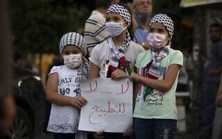 """ילדות פלסטיניות ברמאללה מחזיקות שלט שעליו כתוב """"לא, לא, לנורמליזציה"""" במהלך מחאה נגד ההסכם עם איחוד האמירויות ובחריין עם ישראל, 15 בספטמבר 2020 (צילום: AP Photo/Majdi Mohammed)"""