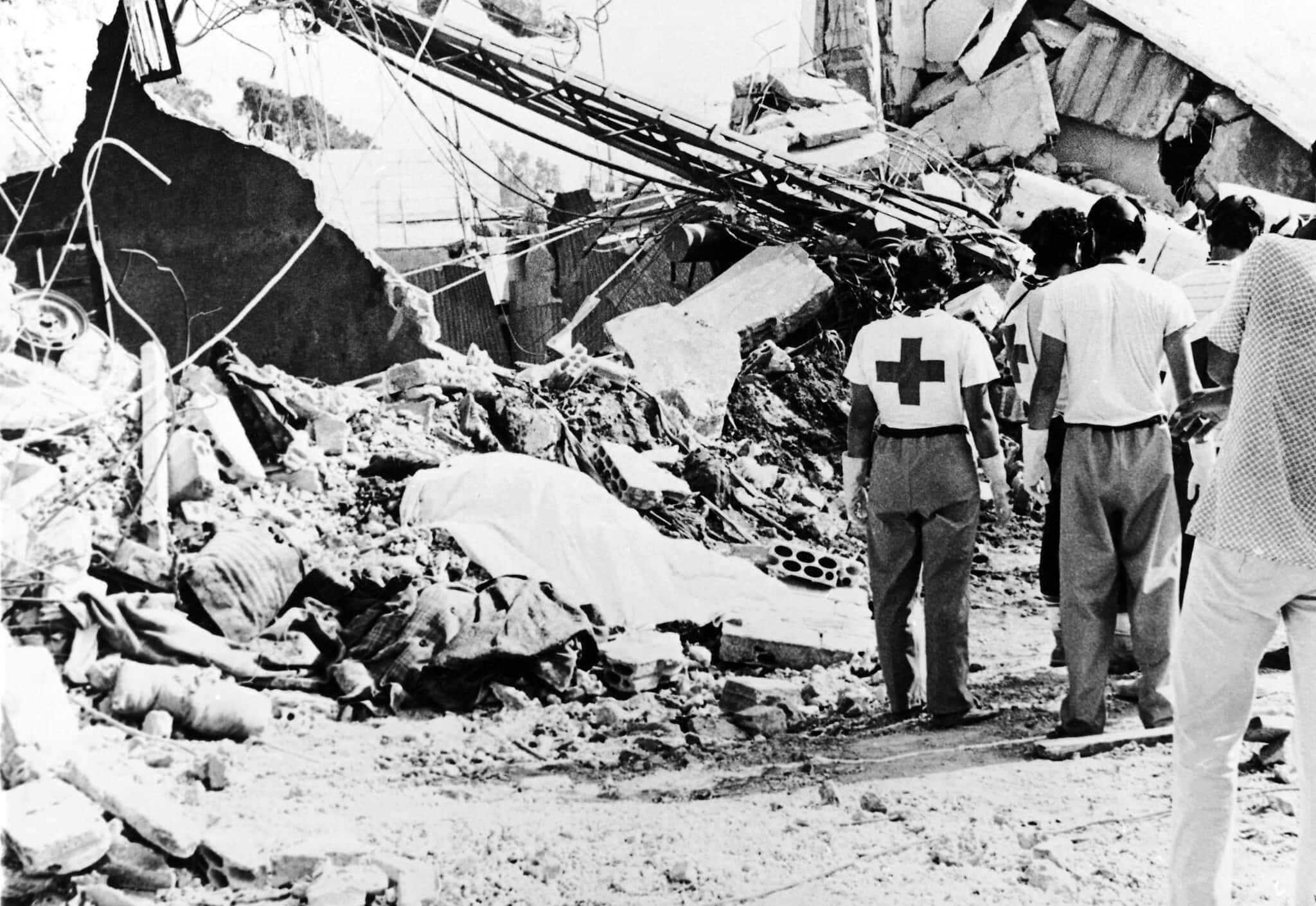 עובדי הצלב האדום מסתכלים על גופה מכוסה בשמיכה זמן קצר לאחר שדחפורים החלו לפנות את השטח במחנה הפליטים סברה בלבנון, 20 בספטמבר 1982 (צילום: (AP Photo/Nash)