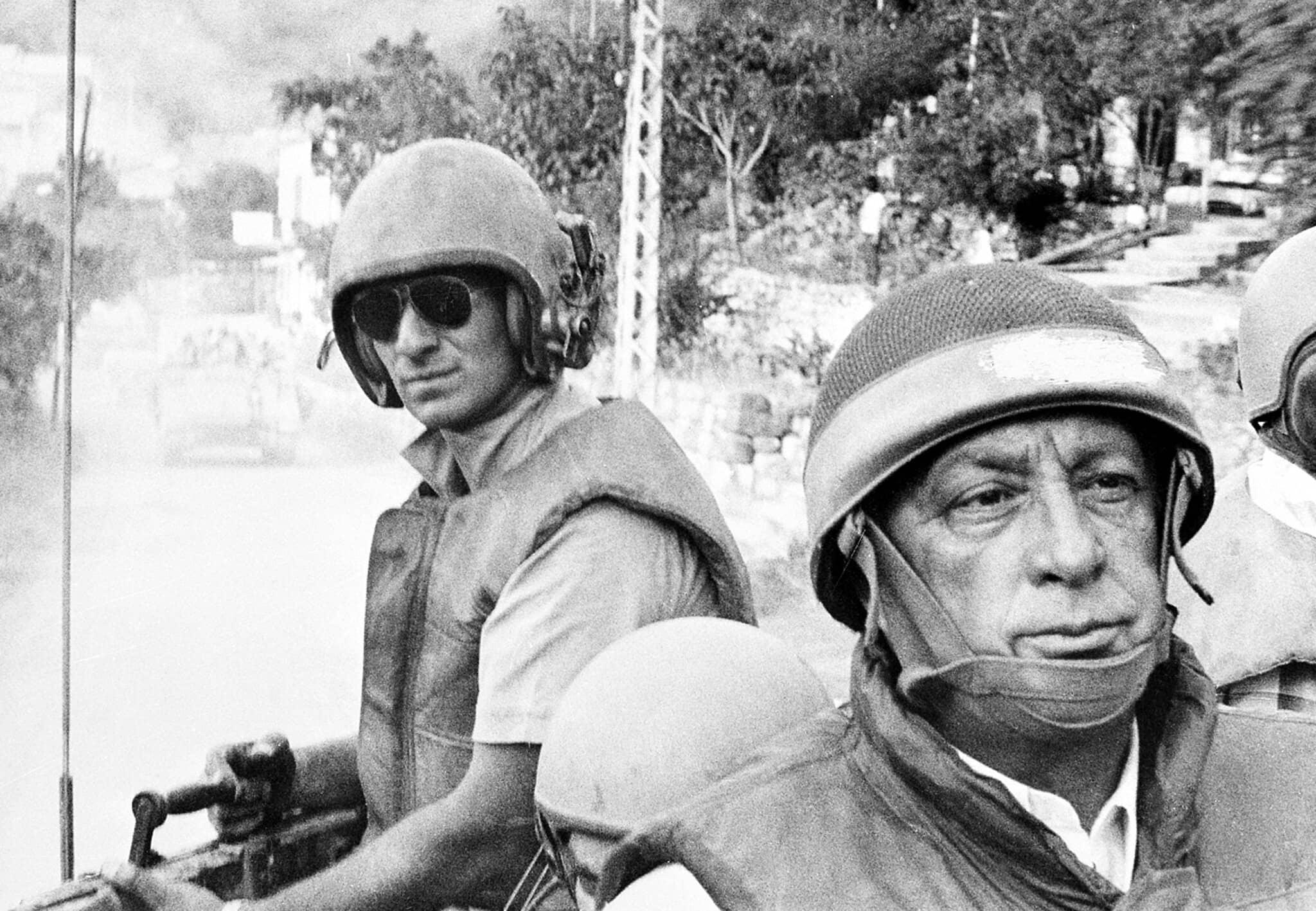 """שר הביטחון דאז אריאל שרון רוכב על נגמ""""ש עם התקדמות הכוחות הישראליים אל פאתי ביירות, לבנון, 15 ביוני 1982 (צילום: AP)"""