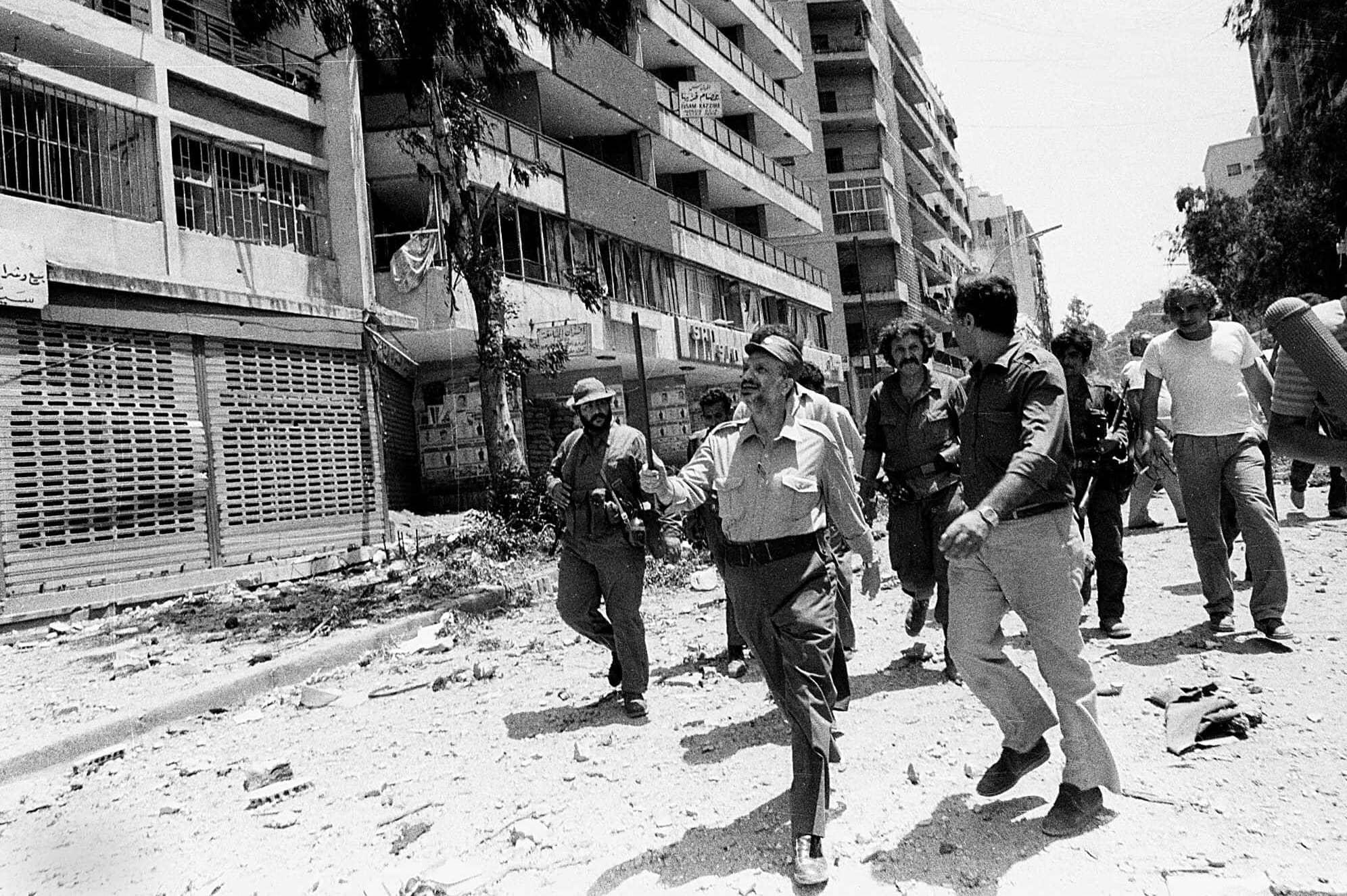 יאסר ערפאת, מקדימה במרכז, בוחן את הנזק באזור האוניברסיטה הערבית במערב ביירות, 2 באוגוסט 1982, בעקבות הפגזה כבדה שביצעה ישראל יום קודם לכן (צילום: AP Photo/Mourad Raouf)