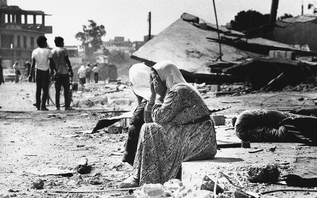 שתי נשים פלסטיניות בוכות על שפת מדרכה במחנה הפליטים סברה במערב ביירות, לבנון, 19 בספטמבר 1982, לאחר שמצאו גופות של קרובי משפחה (צילום: AP Photo/Bill Foley)