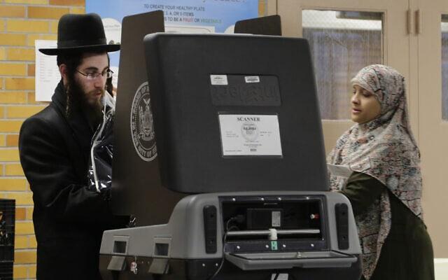 אילוסטרציה, צעיר חרדי מצביע בניו יורק ב-2014. המפקחת על ההצבעה היא מוסלמית (צילום: AP Photo/Mark Lennihan)