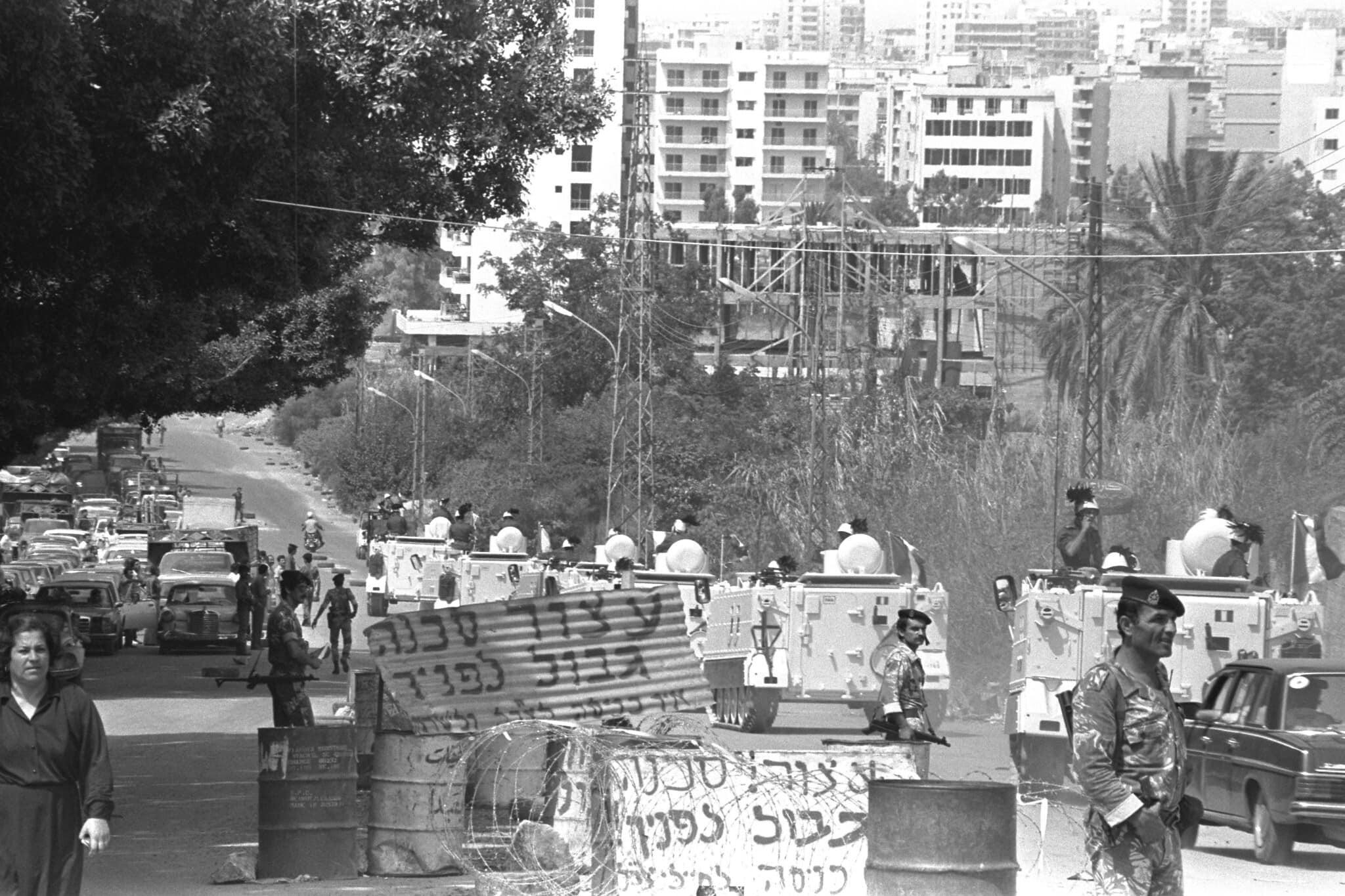 """אילוסטרציה: נגמ""""שים איטלקיים נוסעים במעבר גלרי סמעאן במזרח ביירות, שמאובטח על ידי חיילים לבנוניים אבל עדיין כולל שלטי אזהרה בעברית, 26 באוגוסט 1982 (צילום: לשכת העיתונות הממשלתית/דליה ינקוביץ')"""