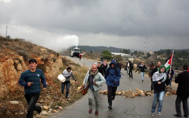 מפגינים פלסטיניים משליכים אבנים בזמן שהמשטרה משתמשת בבואש כדי לפזר מפגינים (צילום: Issam Rimawi/FLASH90)