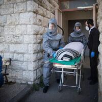 עובדי חברה קדישא נושאים גופה של חולה שמת מקורונה בירושלים, 29 במרץ 2020 (צילום: יונתן זינדל, פלאש 90)