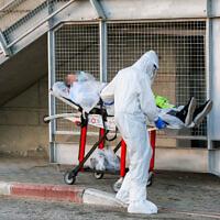 עובד מגן דוד אדום מוביל חולה קורונה לבית חולים בנהריה. יולי 2020 (צילום: David Cohen/Flash90)