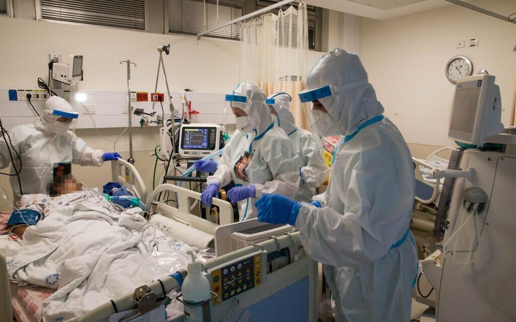 אנשי צוות רפואי מטפלים בחולה קורונה כשהם לובשים בגדי מגן. 23 בספטמבר 2020. (צילום: Nati Shohat/Flash90)