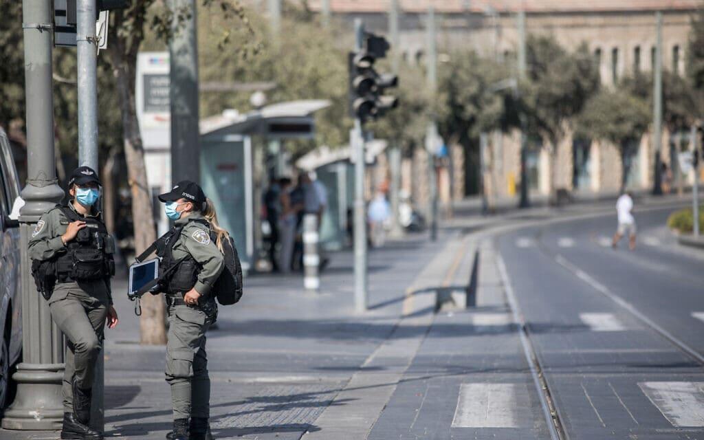 שוטרות על רקע שוק מחנה יהודה הסגור ביום הראשון של הסגר המהודק (צילום: Yonatan Sindel/Flash90)