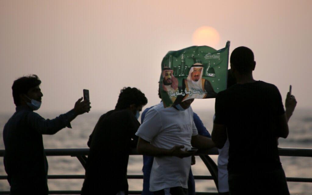 סעודים מציינים את היווסדות המדינה במתכונתה הנוכחית, עם תמונות המלך ויורש העצר, ספטמבר 2020 (צילום: AP Photo/Amr Nabil)