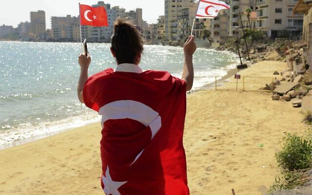אישה מנופפת בדגלי טורקיה וקפריסין הטורקית בקפריסין, 8 באוקטובר 2020 (צילום: AP Photo/Nedim Enginsoy)