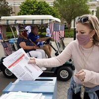 מליסה סטיל-מטובו, העובדת בוועדת הבחירות, משלשלת לקלפי בפלורידה פתקי הצבעה שנבדקו ונמצאו תקינים, 7 באוקטובר 2020 (צילום: John Raoux, AP)
