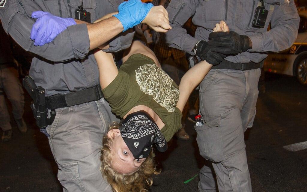 שוטרים גוררים מפגינה מחוץ למעון ראש ממשלת ישראל בנימין נתניהו בירושלים, אוקטובר 2020 (צילום: AP Photo/Ariel Schalit)
