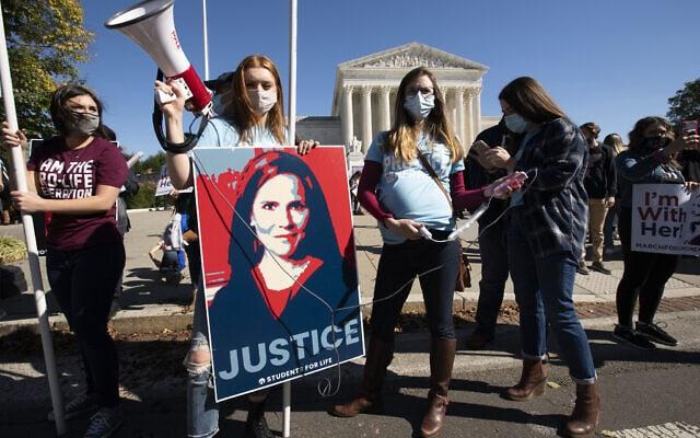 תומכי המועמדת לבית המשפט העליון איימי קוני בארט מתכנסים מחוץ לבניין בית המשפט העליון במהלך צעדת הנשים בוושינגטון, יום שבת, 17 באוקטובר 2020 (צילום: AP Photo/Jose Luis Magana)