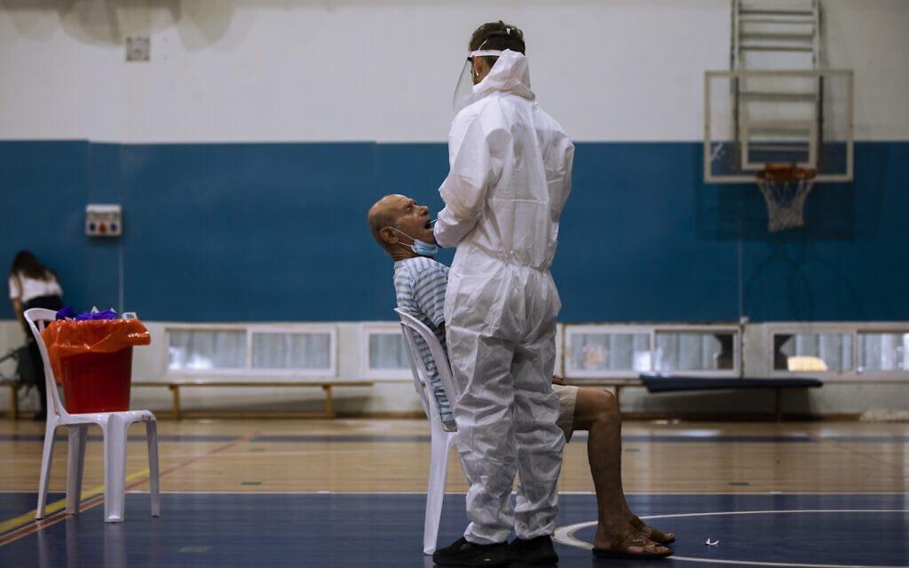 אילוסטרציה, אולם כדורסל ברמת גן הוסב למרכז לבדיקות קורונה, למצולמים אין קשר לנאמר, אוקטובר 2020 (צילום: AP Photo/Oded Balilty)