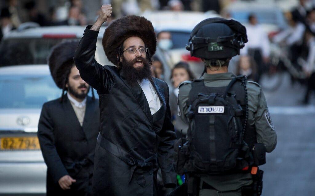 שוטרים מתעמתים עם גברים חרדים בהפגנה נגד אכיפת מגבלות הקורונה במאה שערים בירושלים, 4 באוקטובר, 2020 (צילום: נתי שוחט/ פלאש 90)