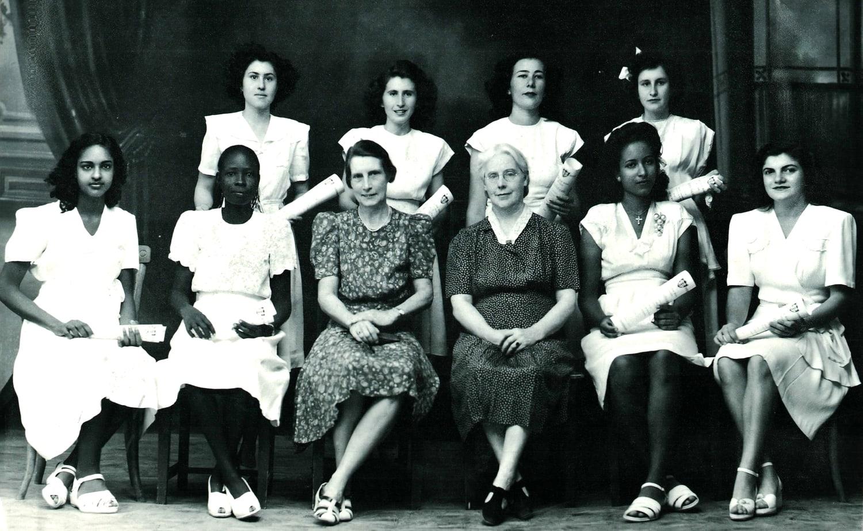 התלמידה היהודייה מרגו (שמאל למעלה) עם חברותיה היווניות, ארמניות, סודניות ומצריות לכיתה, ועם סגל ההוראה הבריטי, בצילום סיום תיכון יוניטי שבו למדה בח'רטום. כל הנערות לובשות שמלות מבהיקות ונעליים בסגנון מערבי (צילום: באדיבות Tales of Jewish Khartoum)