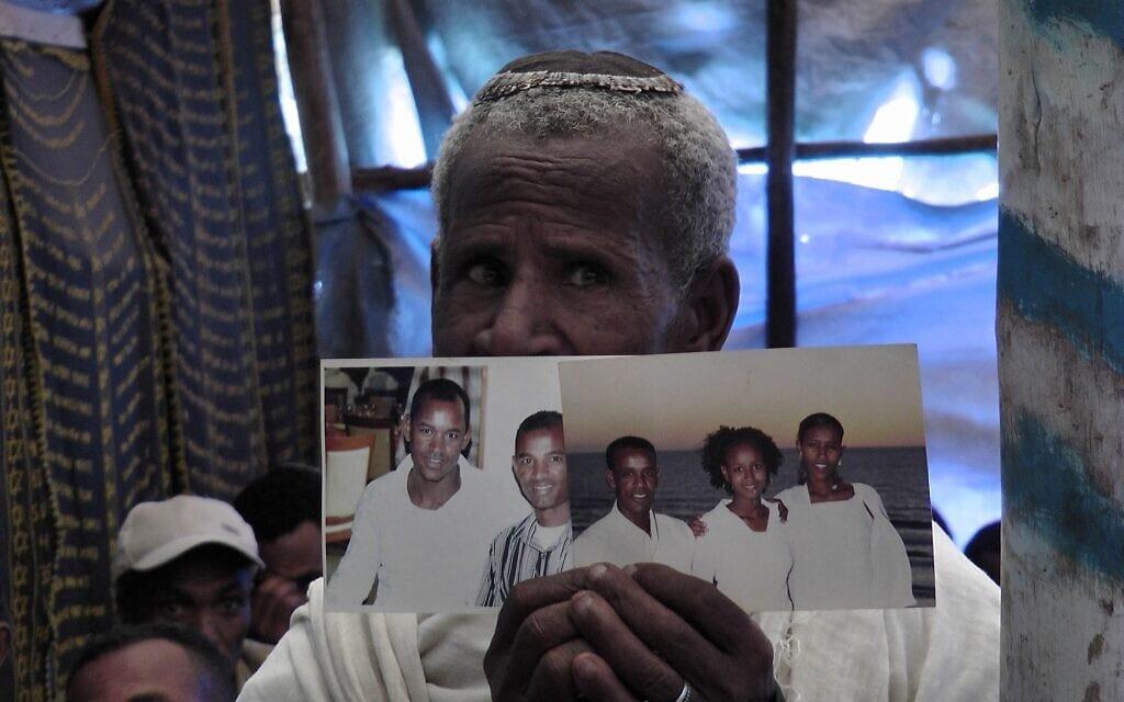 אילוסטרציה, מתפלל בבית הכנסת באדיס אבבה מחזיק בתמונות של בני משפחתו החיים בישראל (צילום: ברנרד דיצ'ק / טיימס ישראל)