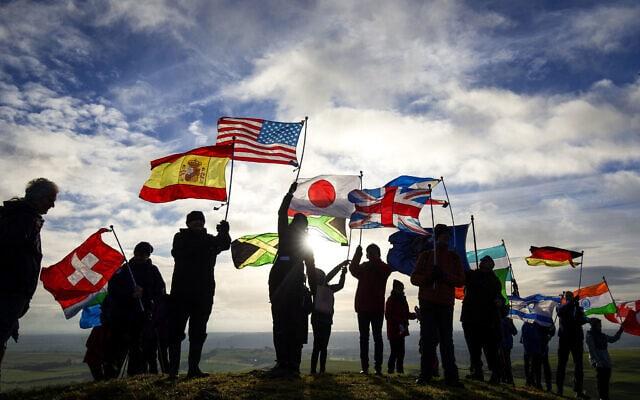 במלאת 30 שניה לאסון לוקרבי, התושבים עומדים במקום ההתרסקות עם 21 דגלים המייצגים את 21 המדינות שאיבדו אזרחים בהתפוצצות מטוס פאן אם 103. 21 בדצמבר 2018 (צילום: Jane Barlow/PA via AP)